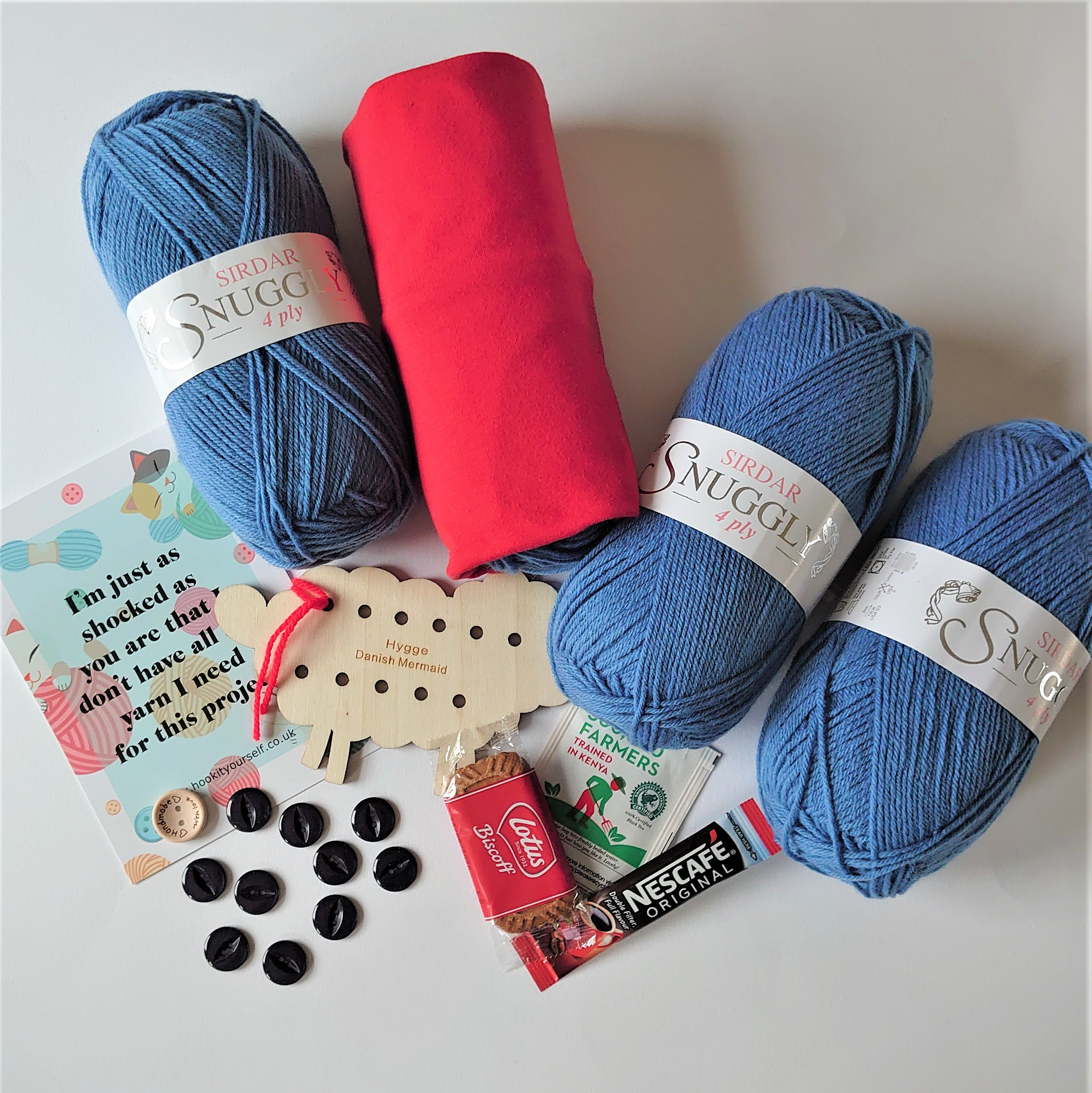 4 balls of Sirdar Snuggly 4ply in blue, with one being encased in a red yarn sock. alongside this there is a postcard which reads 'I'm just as shocked as you are that I don;t have all the I need for this project', blue buttons, tea, coffee and biscuit